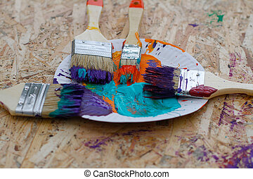 Paints and brushes on OSB board