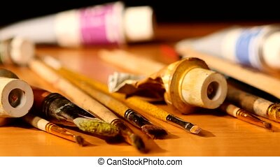 Paints and brushes, tubes of paint on wooden table, black background, cam moves to the right