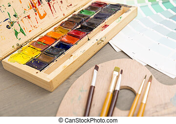 Paints for drawing, palette and brush on a wooden background