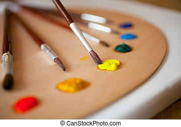 paints on wooden pallet. Focus on paintbrush dipped in yellow pa