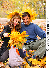 Pair and child with maple leaves on head in autumn wood