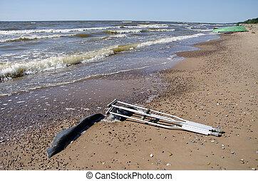 pair crutches on beach sand near sea