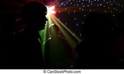 pair dancers dancing in spotlight at the club, silhouette,...