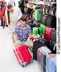 Pair in shop choosing suitcase