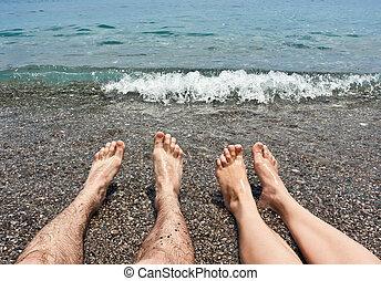 Pair legs on sea beach