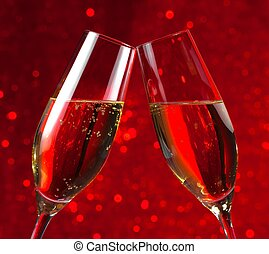 pair of a champagne flutes on red light bokeh background