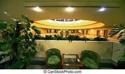 Pair of armchairs at table among plants on top level of multiple floor building