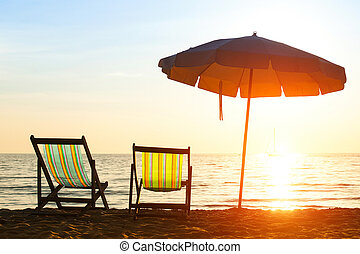 Pair of beach loungers on deserted coast sea at sunrise