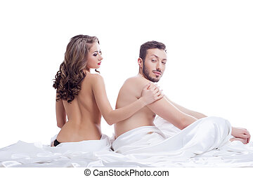 Pair of beautiful young lovers posing in bed