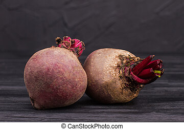 Pair of beetroots on dark background.