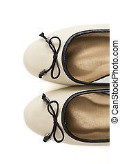 Pair of beige female shoes with black bow over white background