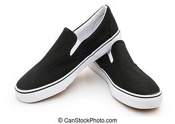 pair of black sneakers on white