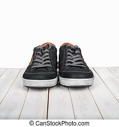 Pair of black sneakers on white wooden background