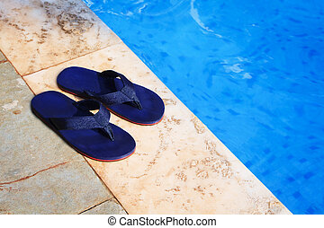 pair of blue flip flops at the edge of a swimming pool