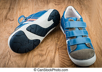Pair of blue sneakers in children size on wooden background