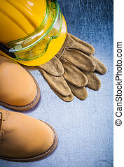 Pair of brown safety lace shoes leather gloves hard hat and work