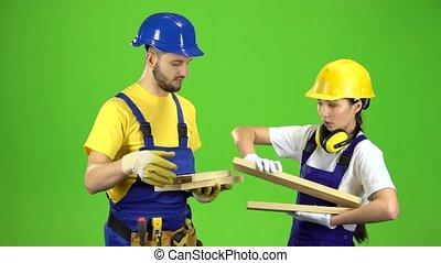 Pair of builders choose wooden boards. Green screen - Pair...