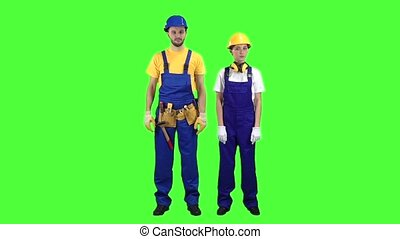 Pair of builders stand and cross their arms. Green screen. Slow motion