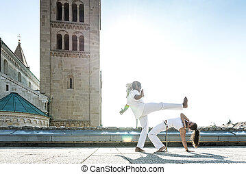 Pair of capoeira performers doing a kicking