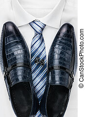 Pair of classic blue shoes standing on a shirt and tie. Men's fashion.