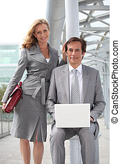Pair of confident executives with laptop computer