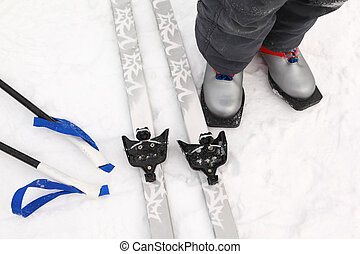 Pair of cross-country ski, ski poles lying and boots of little boy legs on pure white snow