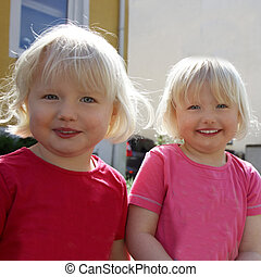 Pair of cute little blond identical twins with mischievous expressions standing looking at the camera, closeup upper body portrait