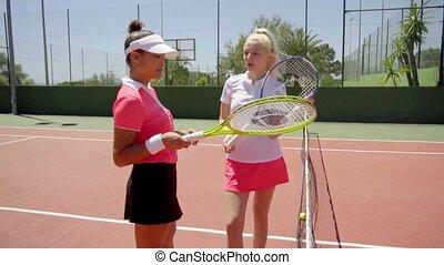Pair of cute tennis players posing near net