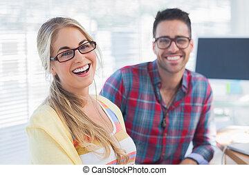 Pair of designers sit in their office - Pair of smiling...