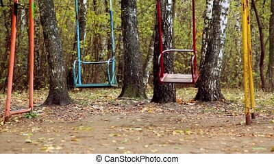 Pair of empty metallic swing sway on grove at autumn day