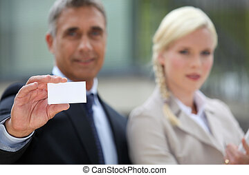 Pair of executives holding up a blank business card