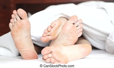 Pair of feet playing footsie under the covers at home in bed