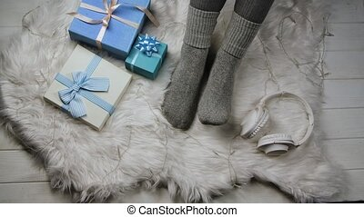 Pair of female feet in gray socks next to blue gift boxes, headphones and a luminous garland. Woman relaxes on white fur. Home comfort concept. Expectation of the winter holidays Christmas and New Year. Close up. Slow motion.