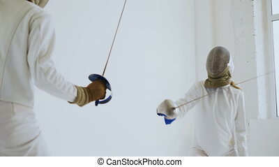 Pair of fencers having practice defence exercises in fencing...