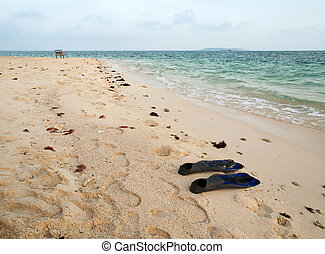 pair of fin on sand beach