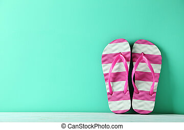 Pair of flip flops on green wooden table