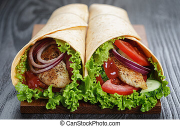 pair of fresh juicy wrap sandwiches with chicken and...