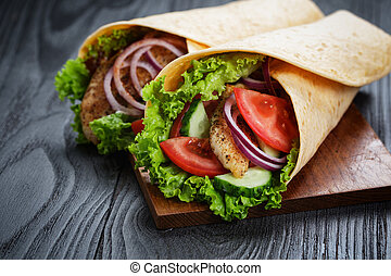 pair of fresh juicy wrap sandwiches with chicken and vegetables