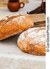 pair of fresh round breads lies on a table covered with a gray tablecloth vertical photo
