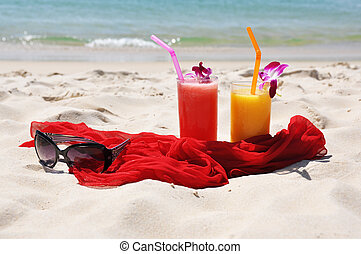 Pair of fruit shakes, red shawl and sunglasses on the beach...
