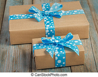 Pair of gift boxes wrapped in kraft paper with blue ribbon bow on old wood boards with vestiges of blue paint.