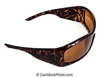 A closeup studio shot of a pair of brown tortoise pattenr plastic sunglasses.