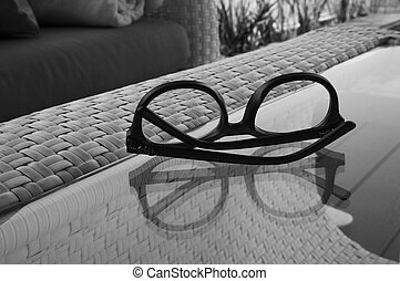 A pair of glasses on the table with reflection in black and white