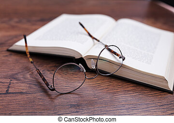 A pair of glasses with a book on wood surface