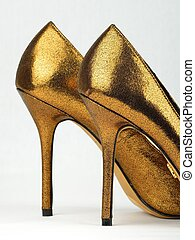 closeup of golden colored High Heel shoes against white background