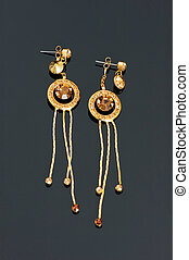 Pair of golden earrings on black reflective surface