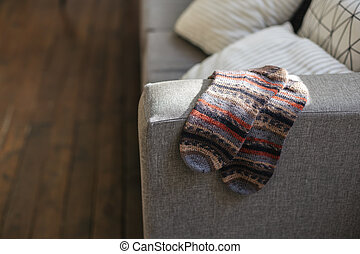 Pair of hand knitted socks on the sofa in modern interior.