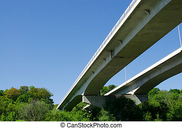 Pair of highway bridges on sky and forest