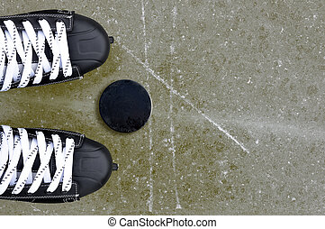 Pair of hockey skates with puck on a ice rink. Winter sport.