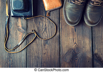 pair of leather brown shoes and an old vintage camera
